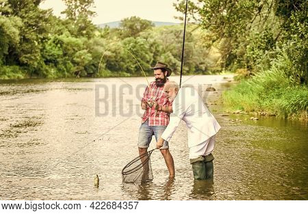 Relax In Natural Environment. Elegant Bearded Man And Brutal Hipster Fishing. Hobby And Recreation.