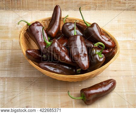 Basket with whole fresh chocolate mini pointed bell peppers close up on wooden background