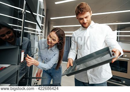 Young Couple Choosing New Electric Oven In Hypermarket