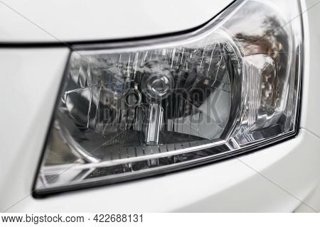 Closeup Of Front Halogen Headlight On  A White Car