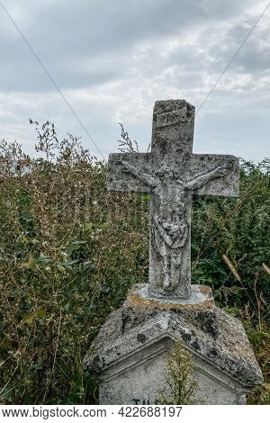 Vertical Image. Unnamed Gravestone On Old Abandoned City Cemetery. Weathered Stone Cross On Abandone