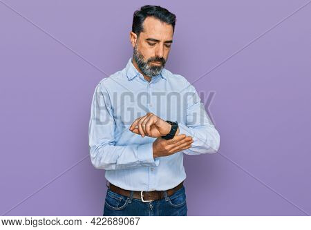 Middle aged man with beard wearing business shirt suffering pain on hands and fingers, arthritis inflammation