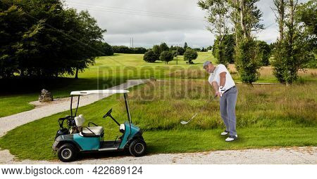 Composition of caucasian man playing golf striking with golf club next to golf cart. championships, sports and competition concept digitally generated image.