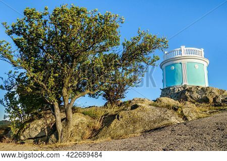 Tree Growing Nearby Tower With Eternal Flame In Kerch, Crimea. Shot On Top Of Mount Mithridat. This