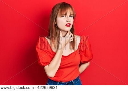 Redhead young woman wearing casual red t shirt touching painful neck, sore throat for flu, clod and infection