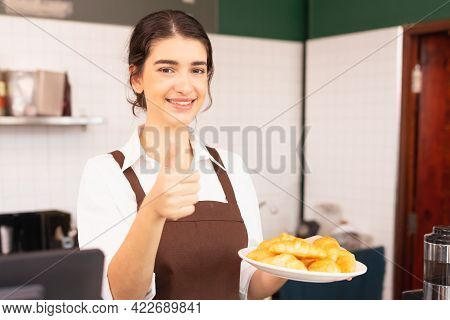 Beautiful Caucasian Barista Woman Looking At Left Side, Holding Plate With Bread On Hand, And Giving