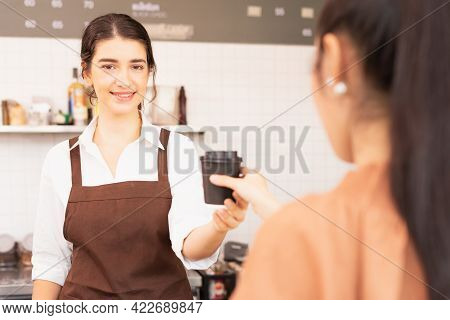 Beautiful Caucasian Barista Woman Give Takeaway Coffee Cup To The Customer And Looking Straight Whil