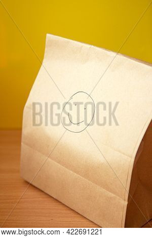 Brown Craft Paper Bag With A Drawn Smile On Yellow Background. Recycled Paper Shopping Bag, Lunch Ba