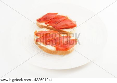 Two open-face sandwiches with smoked salmon on white plate