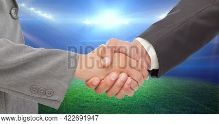 Composition of business people shaking hands over sports stadium. sports, deal, agreement and competition concept digitally generated image.