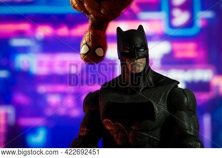 JUNE 1 2021: humor shot of DC Comics Batman with Marvel Comics Spiderman looking over his shoulder - Hasbro action figures