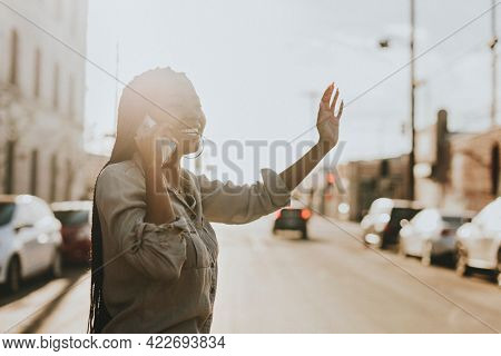 Black woman on the phone hailing a cab