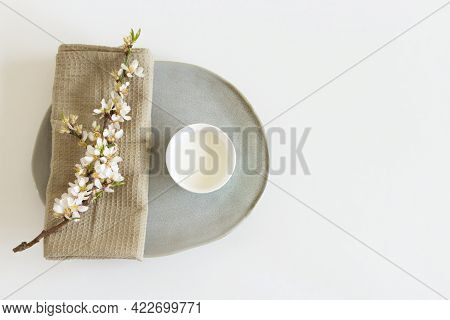 Flowering Branch Of Almond And Cup Of Almond Milk On A White Background.healthy Eating Concept.copy