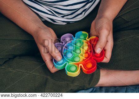 Close Up Of Boys Hands Using Rainbow Pop It Fidget Toy. Push Bubble Fidget Sensory Toy - Washable An