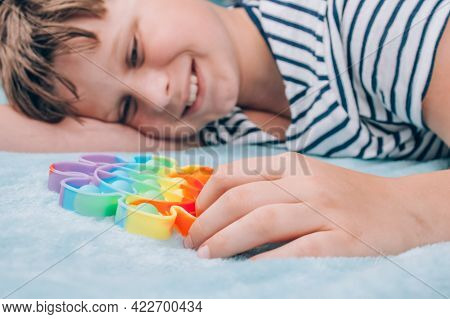 Smiling Boy Playing With Rainbow Pop It Fidget Toy. Push Bubble Fidget Sensory Toy - Washable And Re