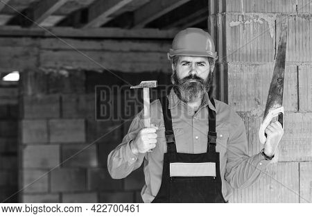 Man Builder In Unfinished Building. Professional Repairman Use Saw And Hammer. Build And Constructio