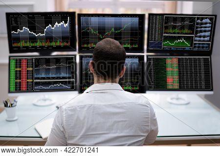 Stock Trader Man Using Multiple Computer Monitors