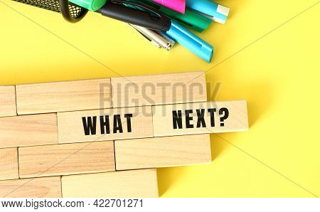 Wooden Blocks Stacked Next To Pens And Pencils On A Yellow Background. What Next Text On A Wooden Bl