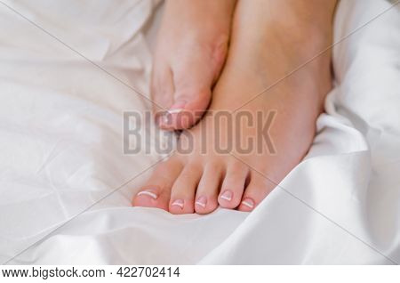 Beautiful Female Tanned Legs On A White Bedclothes In Bed, With A Laconic Pedicure, Relaxed Woman, W