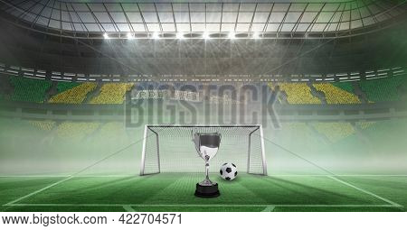 Compostion of cup and football over stadium and goal. championships, sports and competition concept digitally generated image.