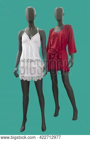 Two Full Length Female Mannequins Wearing Fashionable Nightwear Isolated On A Green Background.