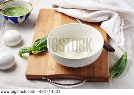 Mozzarella Cheese Ball In A Bowl And Fresh Basil Leaves.
