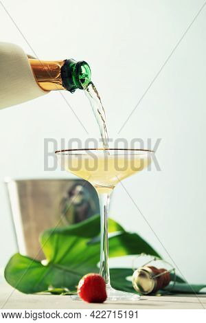 Pouring Champagne Into Glass On Blue Sky Background