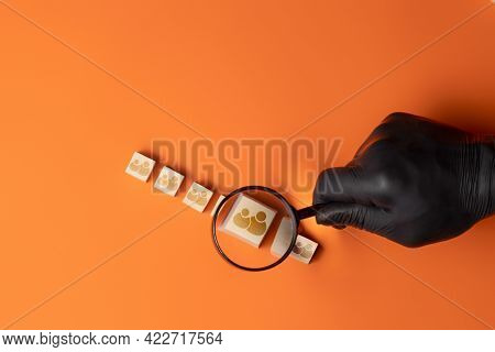 Black-gloved Hand Holding A Magnifying Glass Searches For An Icon Of A Group Of People On A Wooden C