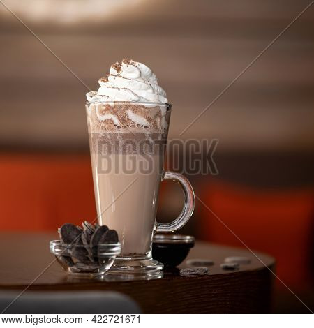 Long Cup Of Macchiato Coffee With Whipped Cream On Top Of It And Glass Bowl With Chocolate Cookies O