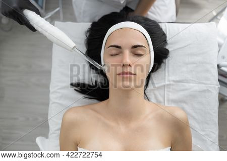 Beautiful Young Woman At The Reception At The Beautician, Galvanic Cleaning Of The Face Using A Curr