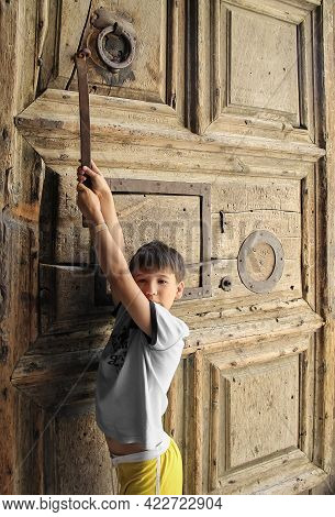 A Boy, Illuminated By The Sun, Is Holding Onto A Large Old Wooden Door Inside The Church Of The Holy