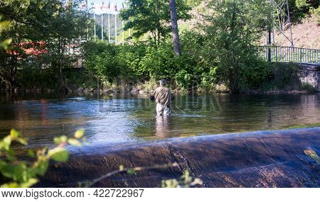 A Fisherman Is Fishing In The River. A Fisherman Stands In The Water In The Middle Of The River.