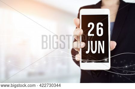 June 26th. Day 26 Of Month, Calendar Date. White Smartphone With Calendar Date In Businesswoman Hand