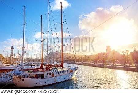 Barcelona Spain. Landing bay at sunset with luxury chic yachts and boats. Cityscape in ray sun.