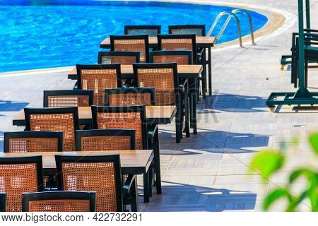 Tables And Chairs Of Outdoor Restaurant Near Swimming Pool At Luxury Hotel