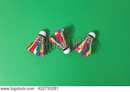 Top View Of Three Feathered Colorful Shuttlecocks On Green Background With Copy Space. Summer Activi