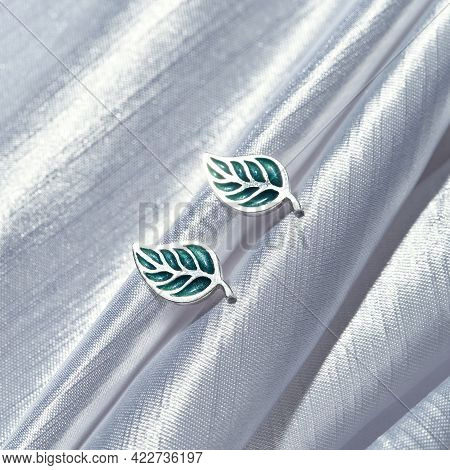 Sterling Silver Stud Earrings In Form Of Leaves Lying On Gray Silk Background. Jewelry Fashion Photo