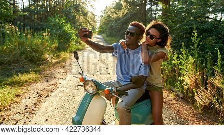Smiling African American Young Couple Taking Selfie While Riding Scooter In Sunny Wood, Widescreen.