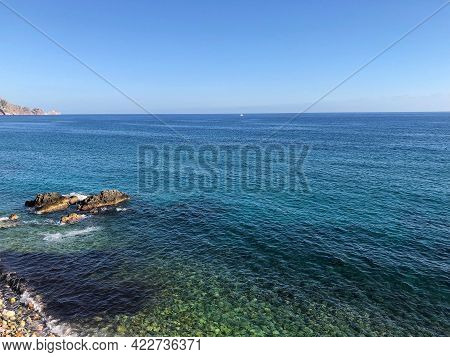 Top View Of The Beautiful Waves Of The Mediterranean Sea Breaking On The Coast Of The Rocky Coast