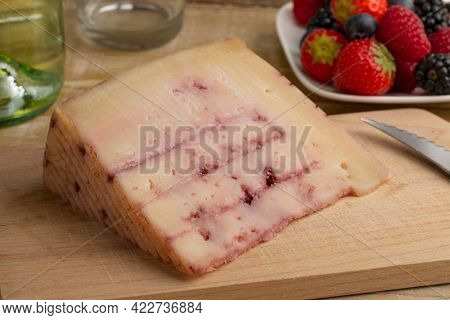Piece of  Spanish goat cheese with red fruit syrup injected inside, on a cutting board and fresh fruit in the background