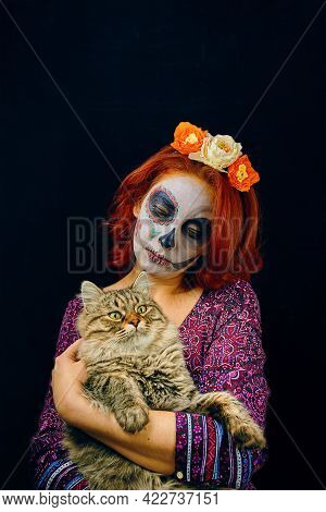 A Young Woman In Day Of The Dead Mask Skull Face Art. Woman With Skull Makeup And Red Hair With Cat