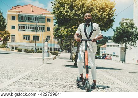 A Dapper Adult Bearded Bald Black Guy In Eyeglasses And A White Fashionable Summer Costume Is Holdin