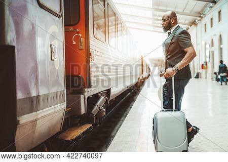 An Elegant Black Business Senior In A Costume And Eyeglasses, With A Bag, Is About To Enter The Rail