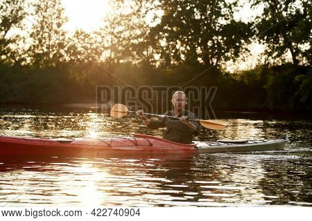 Young Caucasian Guy Paddling Kayak On A Lake Surrounded By Peaceful Nature At Sunset. Kayaking, Trav