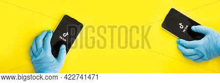 Tver, Russia-may 7, 2020, The Tik Tok Logo On The Smartphone Screen In Hands On Yellow Background. H