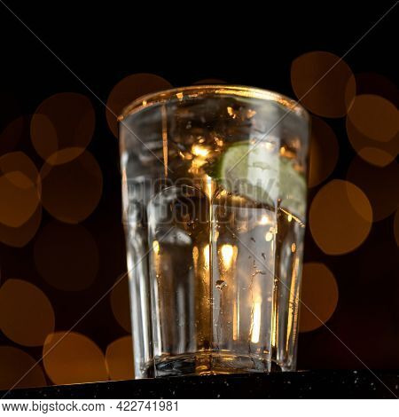 Backlit Glass With Drink Or Beverage At Table On Black Background With Bokeh. Soft Focus. Square For