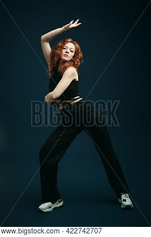 Full length portrait of a professional modern style dancer girl dancing at studio on a dark blue background