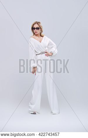 Luxury lifestyle. Full length portrait of a glamorous middle-aged woman in a chic suit and jewelry posing at studio on a white background. Fashion shot.