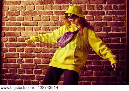 Street dance girl dancing in bright colorful clothes and sunglasses by a brick wall. Modern dances style.