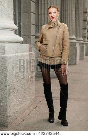 Leather clothing style. Attractive fashion model girl in leather jacket, shorts and leather boots over the knee poses on a city street. Fashion photo.